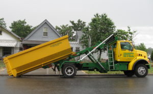 Roll-off truck delivering a rental dumpster in Denver
